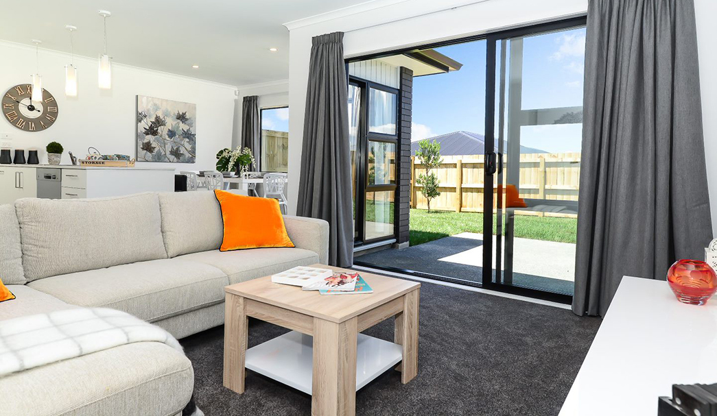 Belmont Village - view of lounge area out through the sliding doors to the fenced garden area